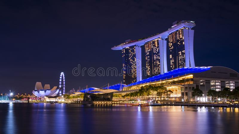 Singapore business building skyline at dawn with reflexion on waterbay in twilight time.Illuminated Marina bay sand at night. Marina bay,Singapore - 2017 stock photo