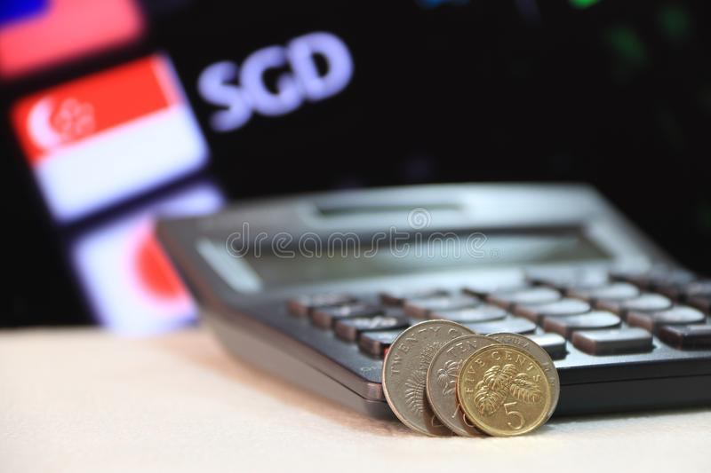 Singapore cents coin SGD with black calculator and digital board of currency exchange money background. Singapore cents coin SGD with black calculator and royalty free stock image