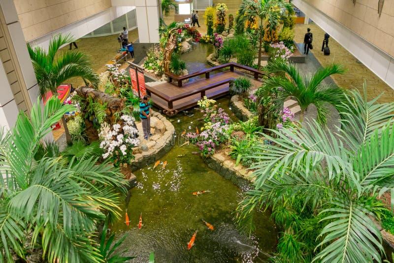 SINGAPORE - CIRCA 23 MAART, 2018: Boven mening van mensen die in een kleine tuin met installaties binnen van Singapore Changi lop stock afbeeldingen