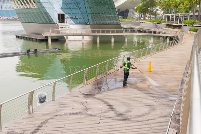 Worker cleaning terrace with a power washer - high water pressure cleaner on wooden terrace surface royalty free stock photo
