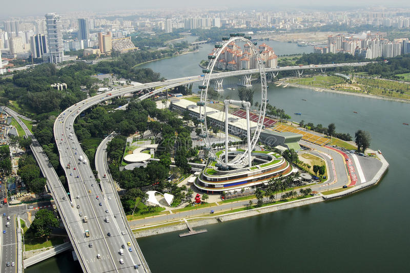 Singapore cityscape. High angle with of Singapore cityscape with curving highway and bridge over sea and ferris wheel stock photo