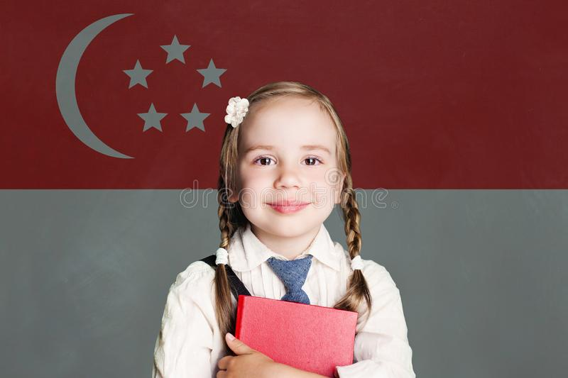Singapore concept with happy child girl in school uniform with book against the Republic of Singapore flag background royalty free stock photography