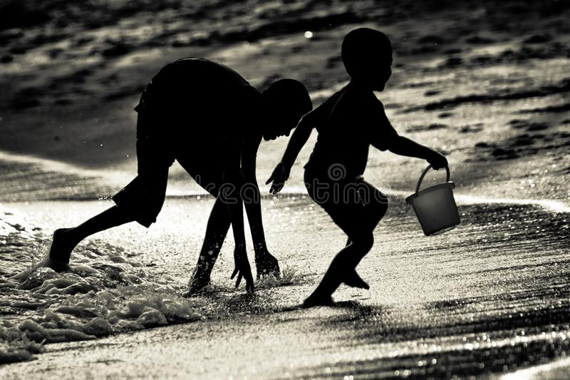 Siblings brothers playing catching at a beach in Singapore royalty free stock photography