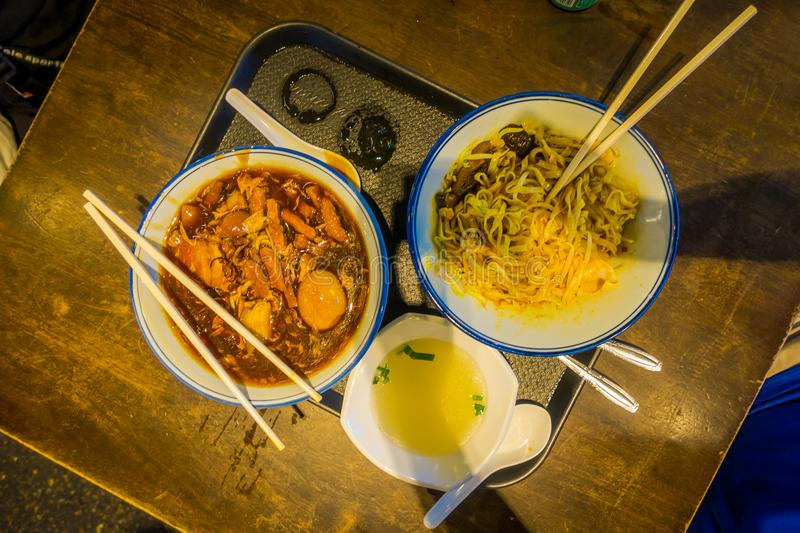 SINGAPORE, SINGAPORE - FEBRUARY 01, 2018: Above view of three plates with food, noodles, chicken and soup over a wooden royalty free stock photo