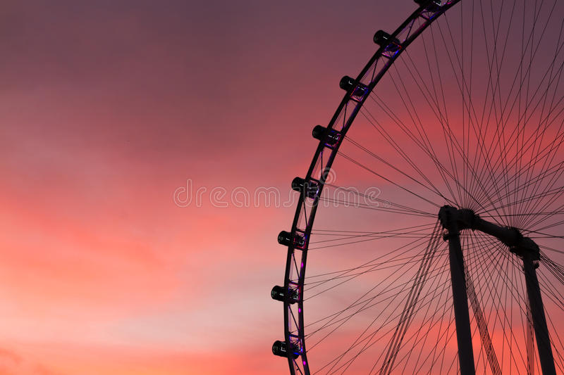 Singapore flyer at twilight. Part of Singapore flyer and skyline at twilight royalty free stock photo