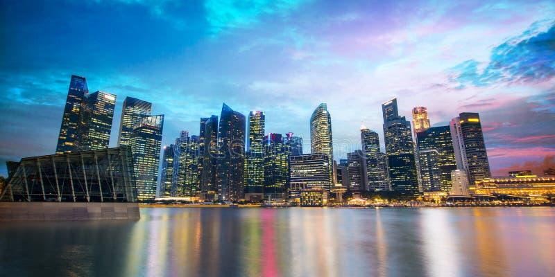 Singapore horisont av det finansiella området vid natt royaltyfria bilder