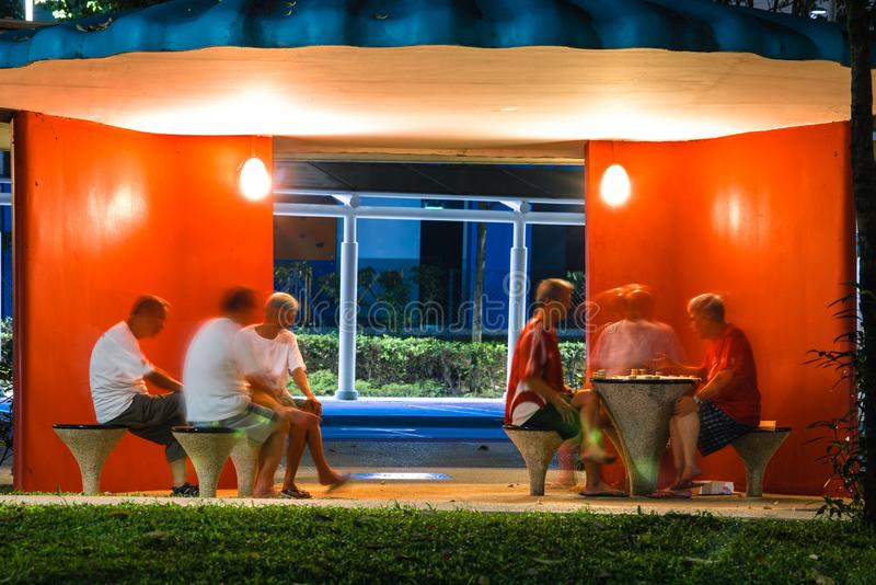 Singapore-05 JAN 2019: old men play chess and talk in a pavilion night view. Singapore-05 JAN 2019: old men play chess and talk in a pavilion stock photos