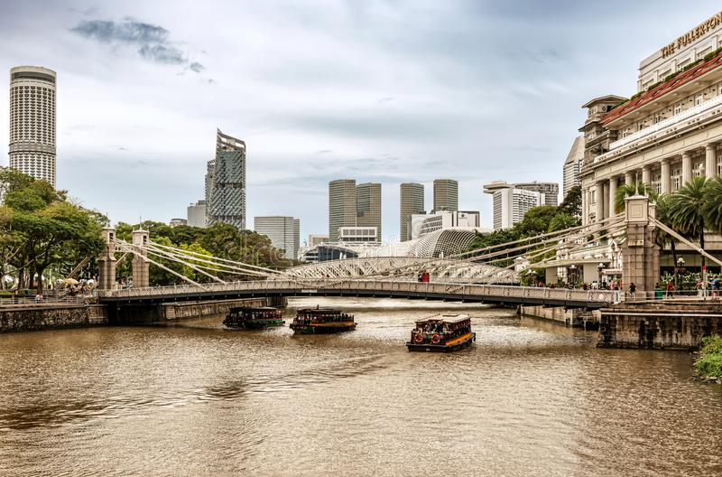 Cavenagh Bridge over the Singapore River. Singapore - Jan 14, 2018: River tour boats with tourists are approaching historical suspension Cavenagh Bridge over the royalty free stock photography