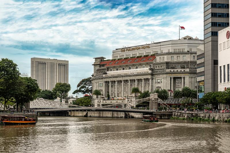 Cavenagh Bridge over the Singapore River. Singapore - Jan 14, 2018: River tour boats with tourists are approaching historical suspension Cavenagh Bridge over the royalty free stock image