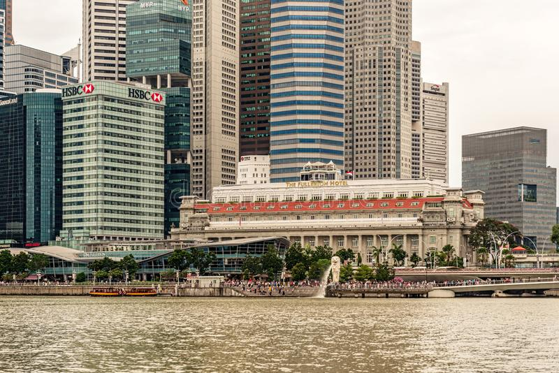 Merlion fountain and Skyscrapers in downtown city of Singapore. Singapore - Jan 14, 2018: Tourists visiting The Merlion fountain at Marina Bay. The Merlion is a stock images
