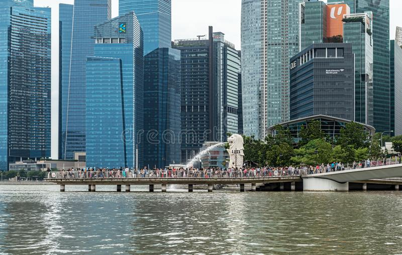 Merlion fountain and Skyscrapers in downtown city of Singapore. Singapore - Jan 14, 2018: Tourists visiting The Merlion fountain at Marina Bay. The Merlion is a royalty free stock images