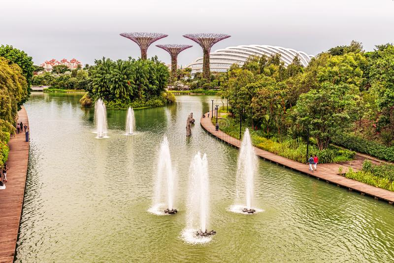 Supertree Grove and Flower Dome in Gardens by the Bay in Singapo. Singapore - Jan 14, 2018: Tourists walking by the dragonfly lake towards Supertree Grove and stock photography