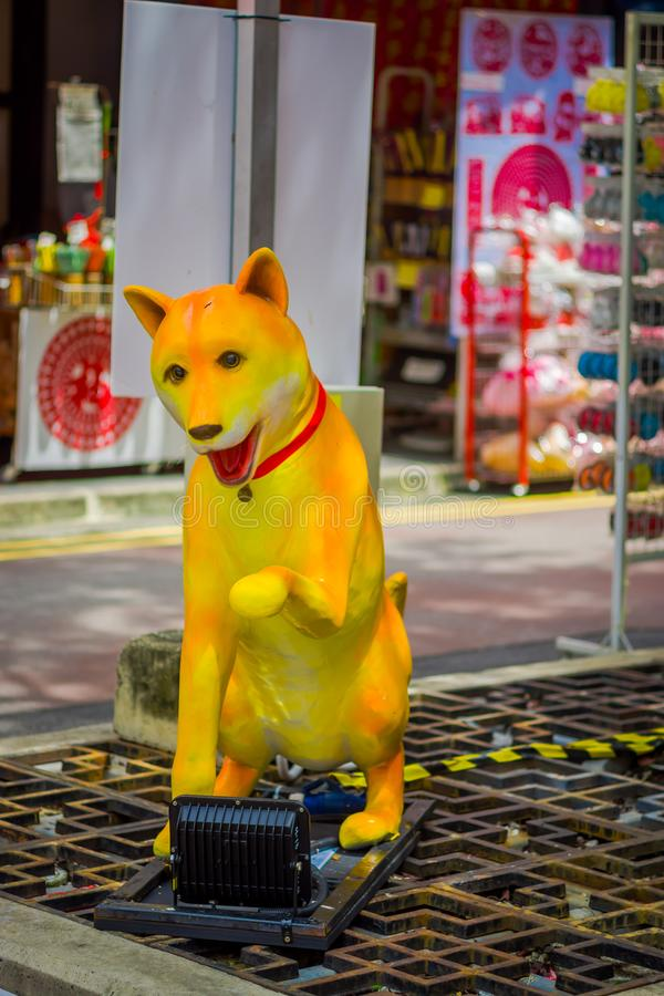 SINGAPORE, SINGAPORE - JANUARI 30, 2018: Openluchtmening van een gele valse die hond in de straten van chinatown binnen wordt gev stock foto
