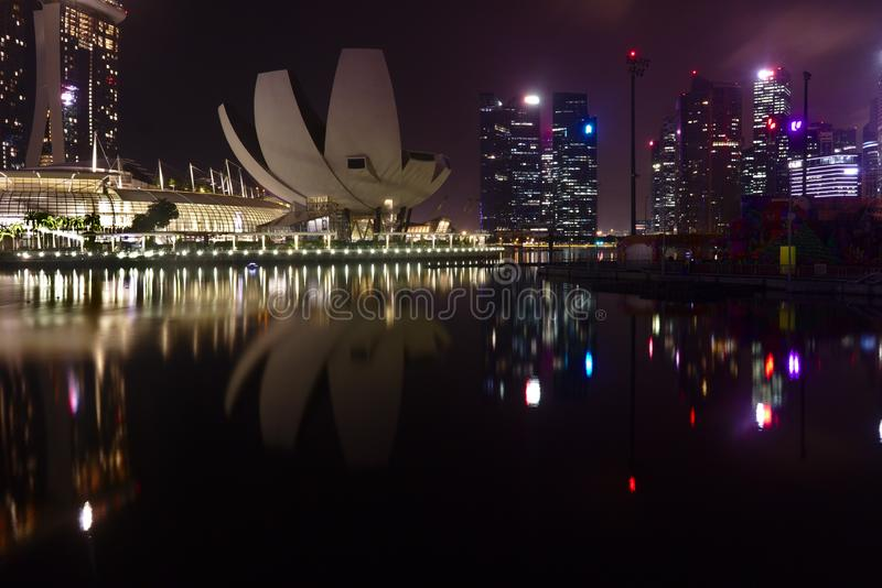 Artscience Museum and Commercial Buildings in seen at Marina Bay during night time with stock photos