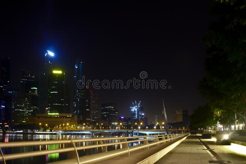 Pathway with commercial buildings seen during nigh time in Marina Bay stock images