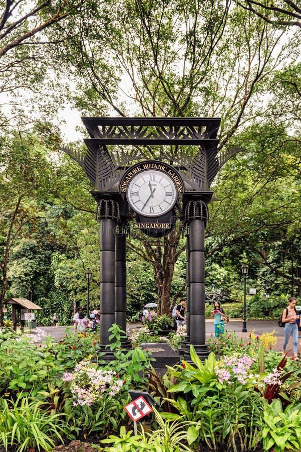 Clock Tower located in Singapore Botanic Gardens. Singapore - January 11, 2018: Tourists are entering Singapore Botanic Gardens passing by clock Tower located stock photos