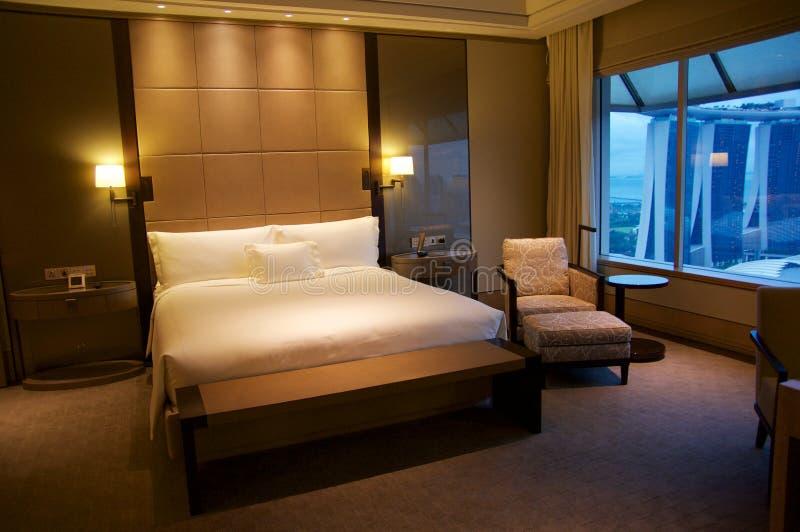 SINGAPORE - JULI 23rd, 2016: lyxigt hotellrum med den moderna inre, en bekväm säng och en enorm sikt av marina arkivbilder