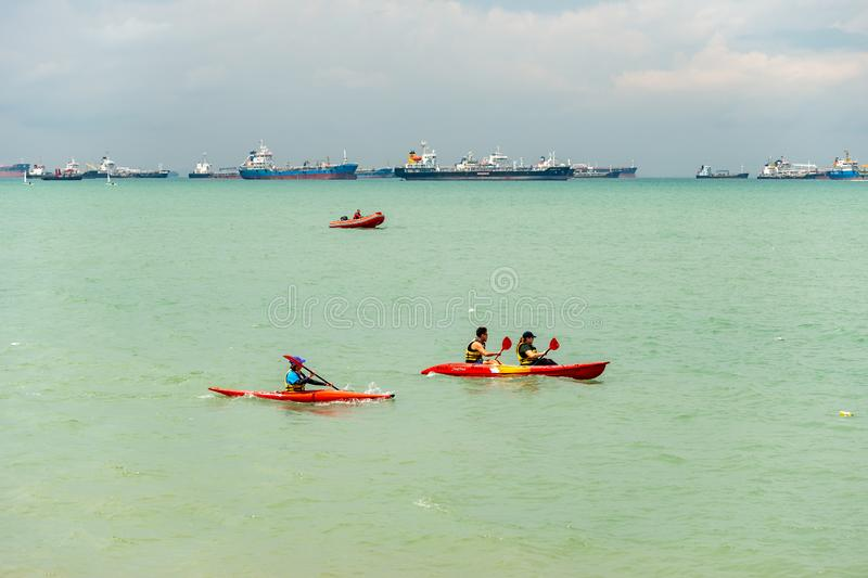 Group of asian sportsmen sportswomen canoeing in the sea under hot sunny weather stock photography
