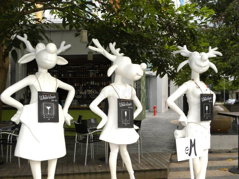Singapore - Juni 1 die, standbeeld van de de kleurenkunst van 2009 het Witte van drie vrouwelijke bokdeers rokken dragen stock afbeelding