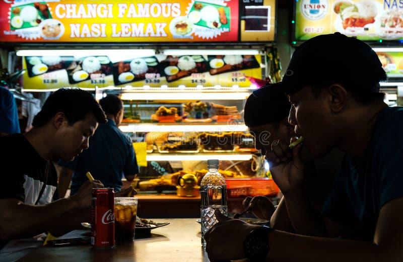 Singapore-29 JUNI 2019: folk som äter lemak för singapore lokal kokkonstnasi i matdomstol royaltyfri bild