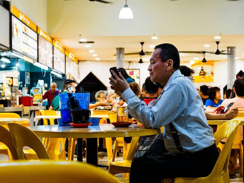 SINGAPORE - 17 MARS 2019 - en mitt åldrades atire för mannen tycker om i regeringsställning ett sent - nattöl på en eatery/coffee royaltyfri fotografi