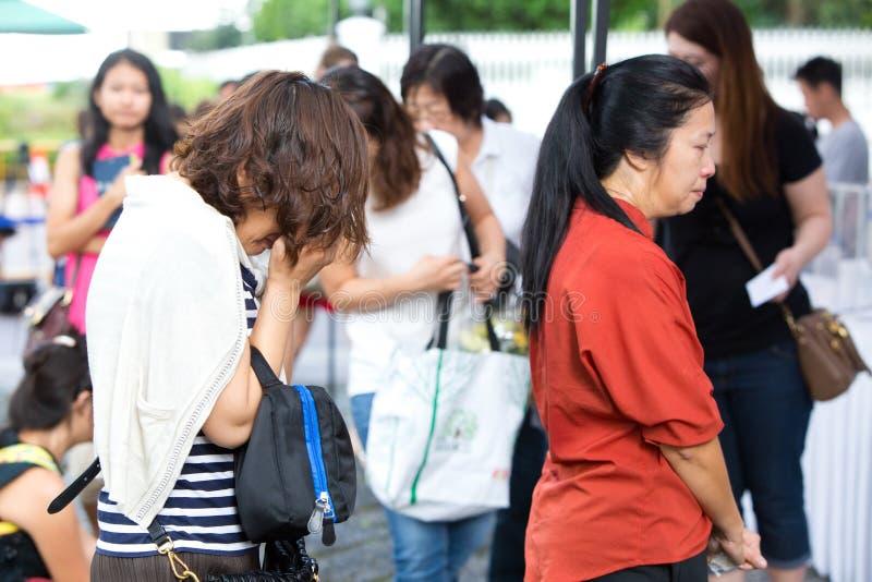 Singapore 24 marzo Una donna grida mentre rende omaggio a Lee Kuan Yew recente, ex primo ministro di Singapore immagini stock libere da diritti