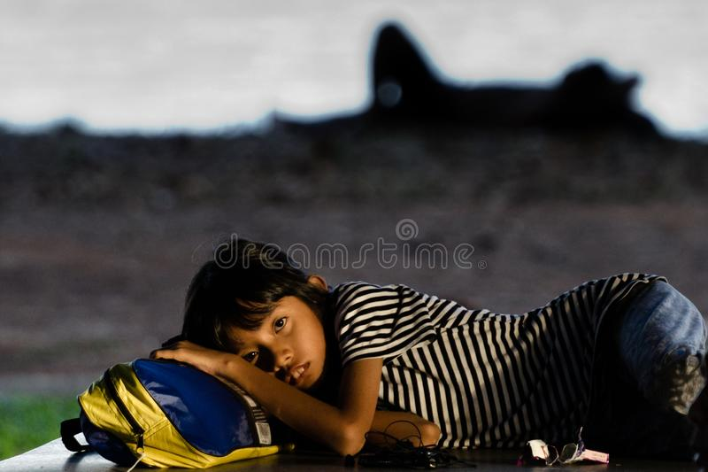 Homeless girl lays on her backpack on the street of Singapore royalty free stock photography