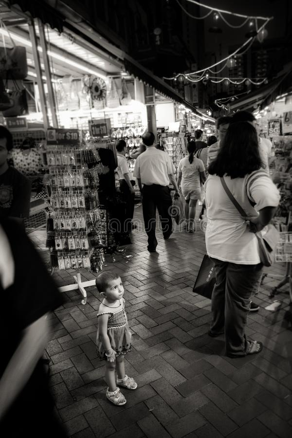Young child looks lost in crowded chinatown street, Singapore royalty free stock photos