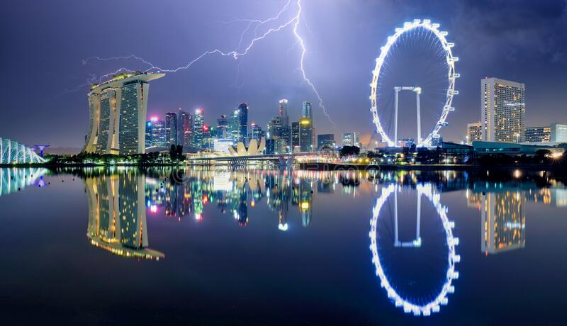 Singapore at night with storm and lightning bolt.  stock photos