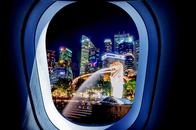 Beautiful city view of The Merlion fountain at night in Singapore from plane window stock photos