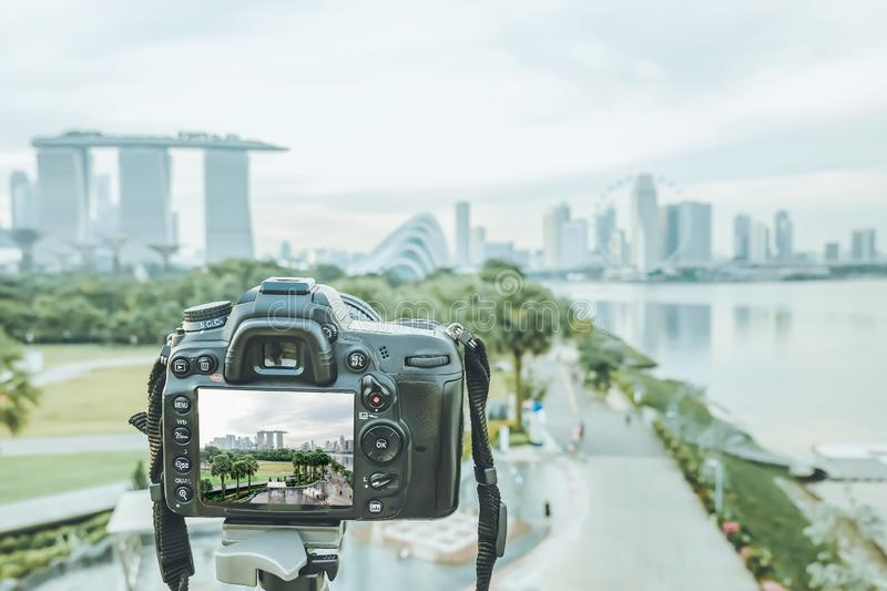 Travel photographer shooting landscape of singapore city during the sunset with professional DSLR camera royalty free stock photo
