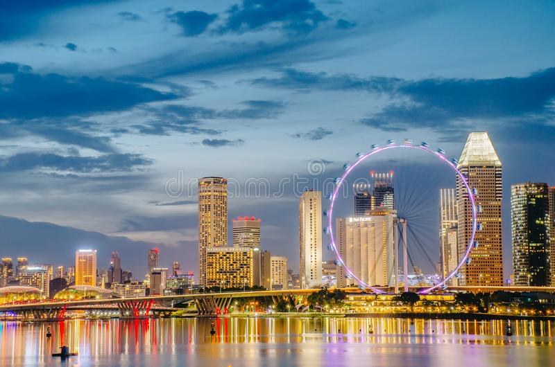 View of the Giant Ferris wheel and Singapore city building background in sunset time stock images