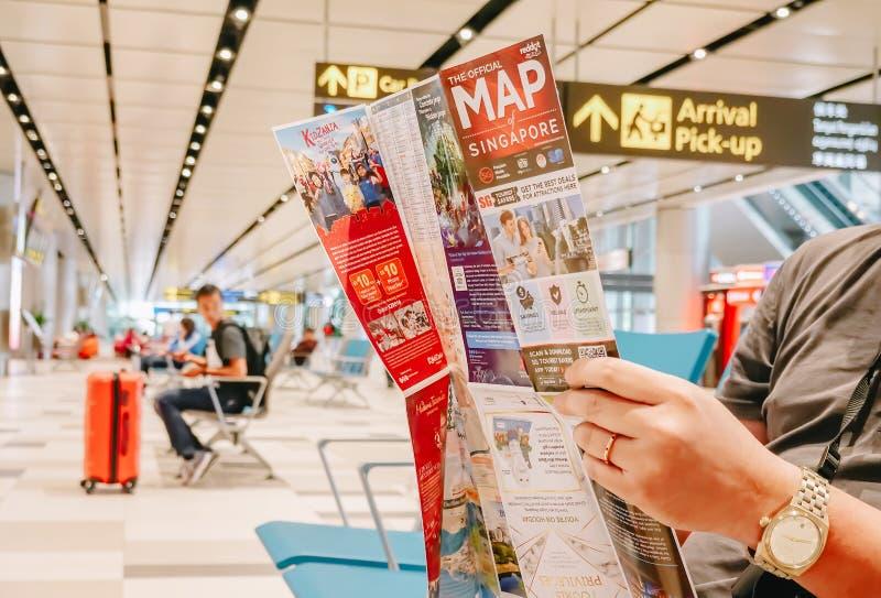 SINGAPORE - NOVEMBER 22, 2018: Loppsemesterbegrepp Asiatisk man i flygplatsläsningöversikt, medan vänta på taxien eller bussen me arkivfoto