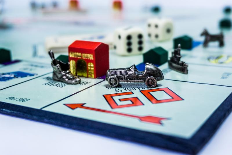 Monopoly Board Game - close up view. Singapore - November 7, 2017: Monopoly Board Game with the car passing the GO. The classic real estate trading game from stock photos