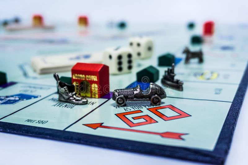 Monopoly Board Game - close up view. Singapore - November 7, 2017: Monopoly Board Game with the car passing the GO. The classic real estate trading game from royalty free stock photo
