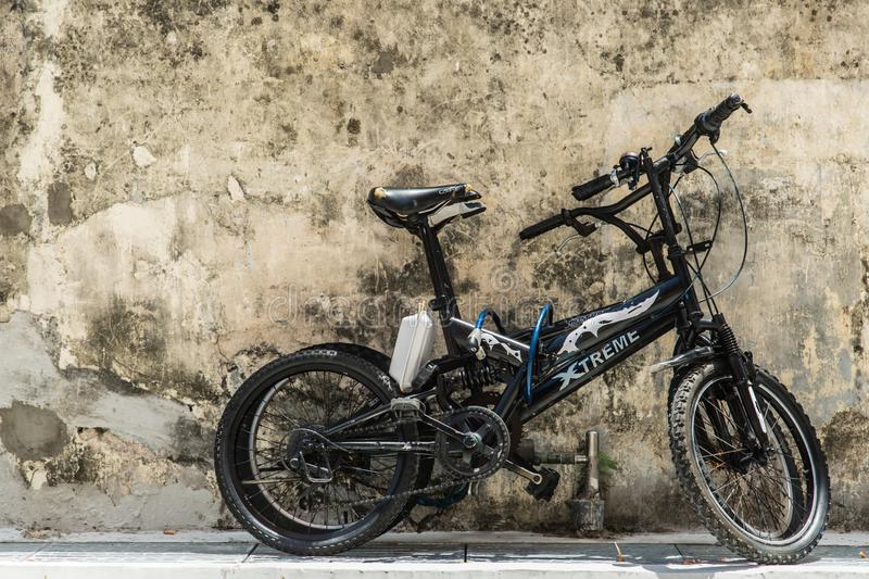 Singapore-17 OCT 2017: old rusty bike park beside the grey wall. Singapore-17 OCT 2017: old rusty bike park beside grey wall stock photos