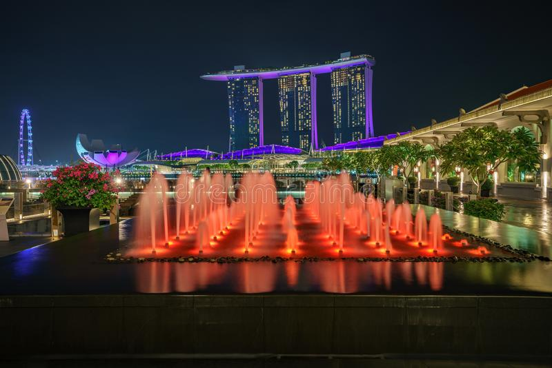 Singapore - october 14, 2018: water fountains in front of marina bay sands and singapore flyer at night. Colorful water fountains in front of marina bay sands stock images