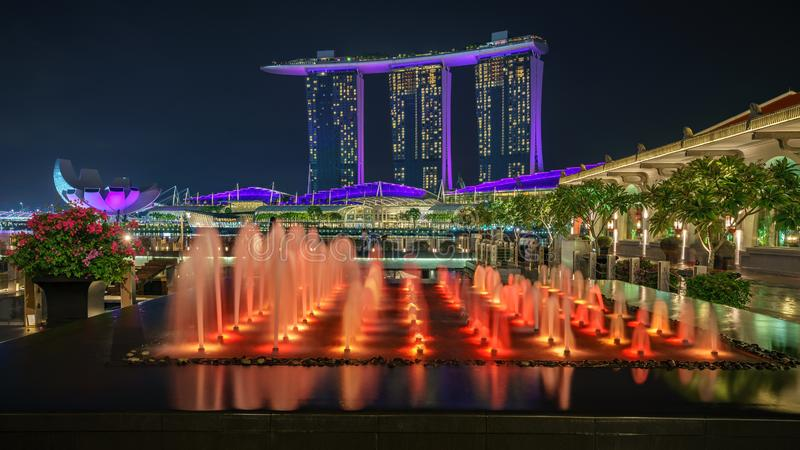 Singapore - october 14, 2018: water fountains in front of marina bay sands and singapore flyer at night. Colorful water fountains in front of marina bay sands royalty free stock photography