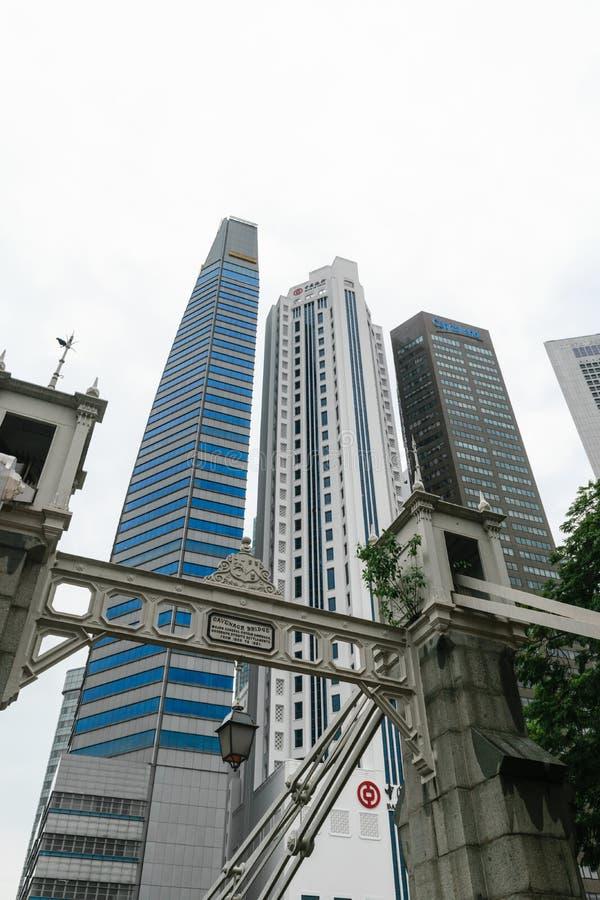 Singapore - 14 OKTOBER 2018 Affärsområde med moderna skyskrapor, bron och molnig himmel fotografering för bildbyråer