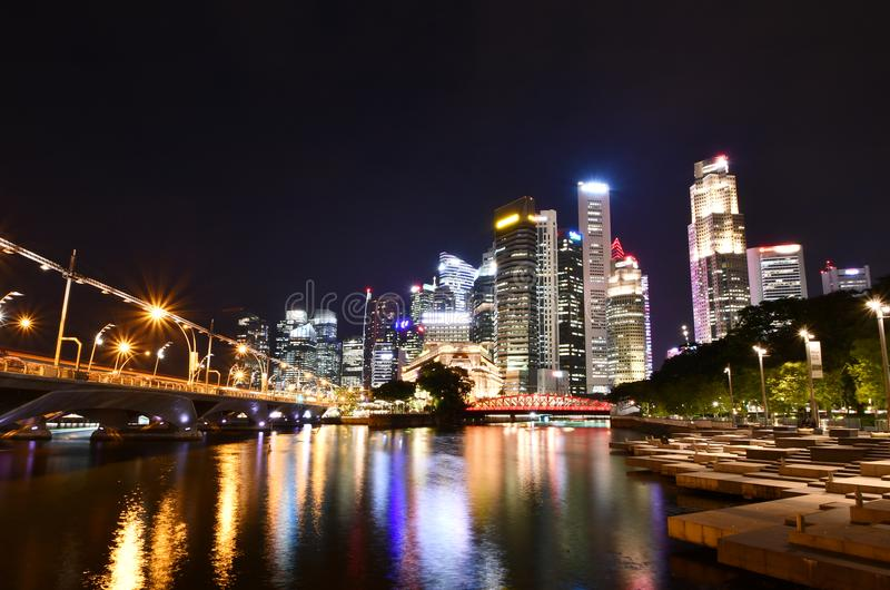 Singapore River Stepped Plazas at Night. Night shot of the stepped plazas flanking the mouth of the Singapore river. The Singaporean skyline can be partially stock photography