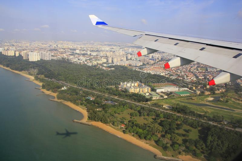 Singapore`s clean, green coastline is seen from aircraft approach landing stock photography