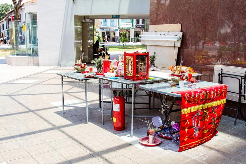 Makeshift Altar for Hungry Ghost Month. SINGAPORE - SEPTEMBER 7, 2017: A makeshift Chinese altar was erected at a street corner to make offerings to spirits stock image