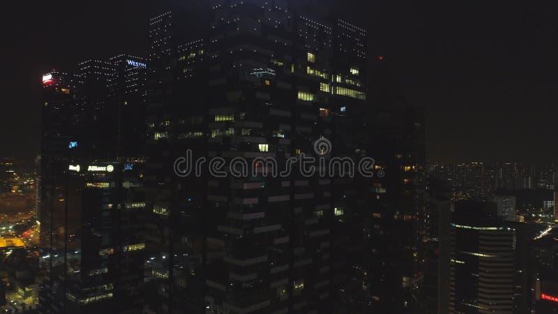 Singapore - 25 September 2018: Windows med folk som arbetar i inre av en kontorsbyggnad på natten i storstaden arkivbilder