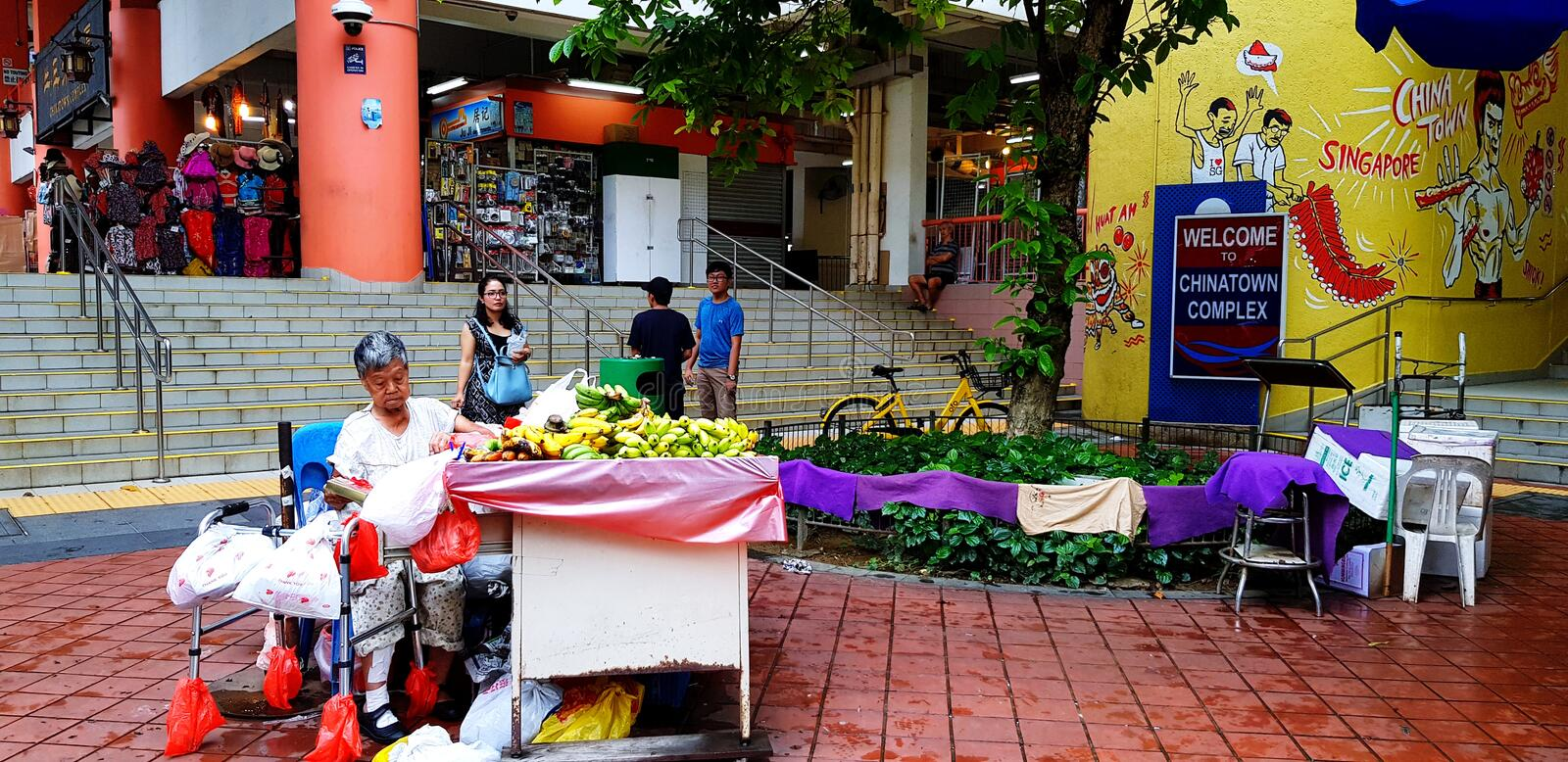 Singapore, Singapore- June 29, 2018: Old woman selling fruit on street food market with blurred people and many shop background stock photo