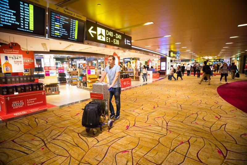 SINGAPORE, SINGAPURE - 12 11 2017: Uomo con il carrello dei bagagli dentro dell'aeroporto di Singapore Changi in Singapure fotografia stock