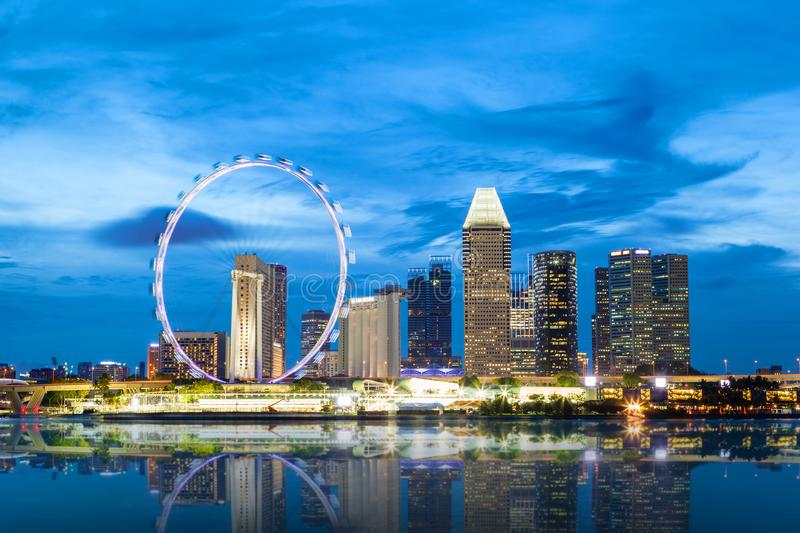 Singapore Skyline at Marina Bay During Sunset Blue Hour. Showing skyscrapers in downtown and giant ferris wheel in motion royalty free stock image