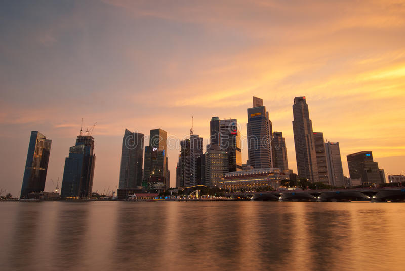 Singapore skyline at sunset. SINGAPORE - APRIL 14: Beautiful sunset view of Singapore skyline with reflections in the water bay taken on April 14, 2010 in stock photos