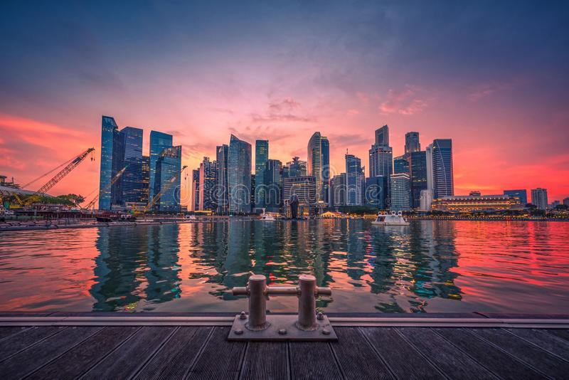 Singapore Skyline and view of business district downtown with wooden walkway on Marina Bay at sunset. stock image