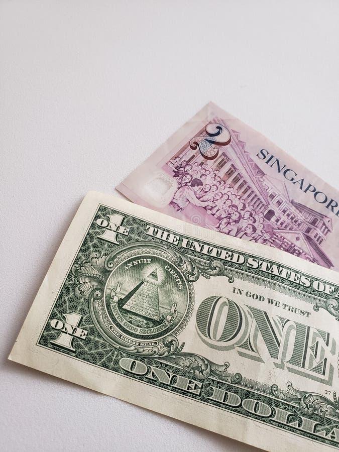 Singaporean bankbiljet van twee dollars en Amerikaanse dollarrekening stock foto