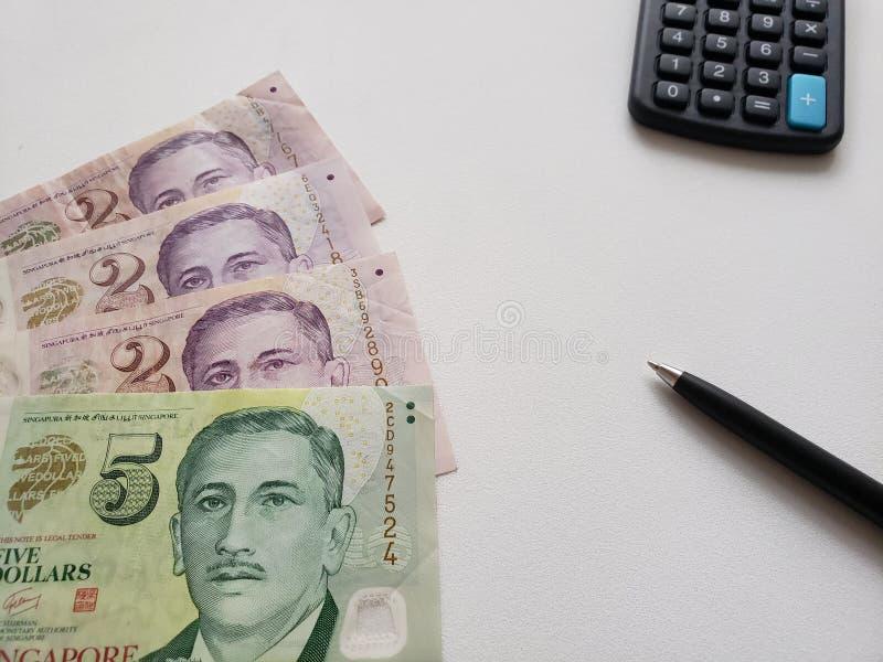 Singaporean bankbiljetten, calculator en zwarte pen op witte achtergrond stock foto's